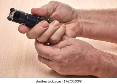 Hands hold a small black flashlight to replace the used battery - Shutterstock ID 1967386099