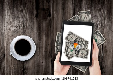 hands hold the tablet on a background old table, coffee and money