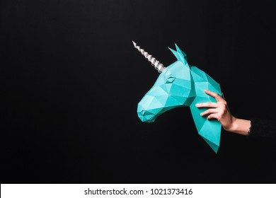 Hands hold a turquoise Unicorn. Artwork. 3d papercraft model of a unicorn. Copy space