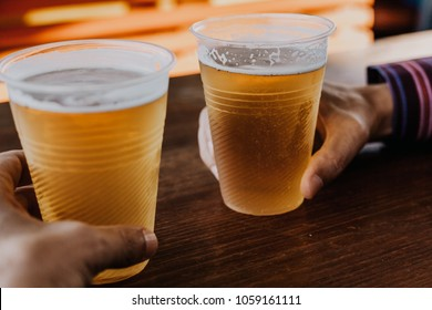 Hands hold two misted single-use plastic glasses with beer stand side by side on a dark background