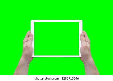 Hands hold white tablet in a horizontal position. View from first person. Isolated screen and background in green.
