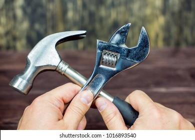 Hands hold a wrench and a hammer