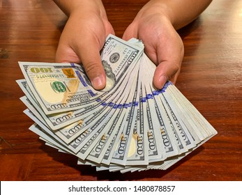 Hands holding 100 dollar bills. Men's hand holds a fan of dollars on wooden table.  Wealth, financial flows and success.