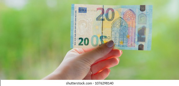 Hands holding 20 euro banknote on the green background. Check euro for authenticity