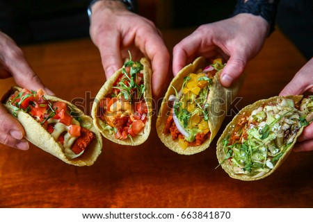 Hands Holding Assorted Mexican Tacos