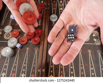 Hands holding Backgammon red and gray discs and black dice over a game board.