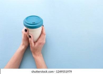 Hands holding bamboo reusable takeaway cup with lid on, on blue background.