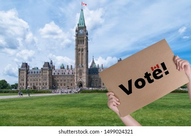 Hands holding banner call to vote in front of Ottawa parliament hill during summer time