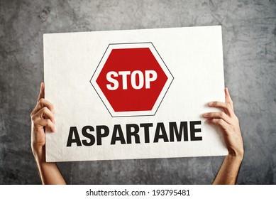 Hands holding banner with STOP ASPARTAME message. Healthy nutrition concept.