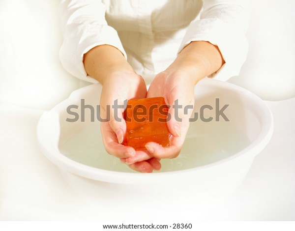 Hands holding a bar of transparent orange soap over a bowl of water. Very high key.