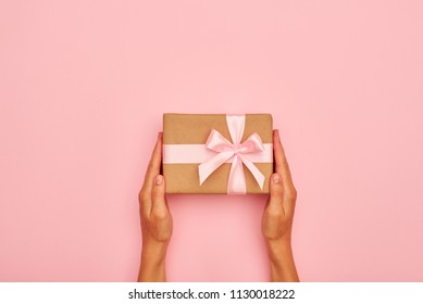 Hands holding beautiful gift box on pink flatlay