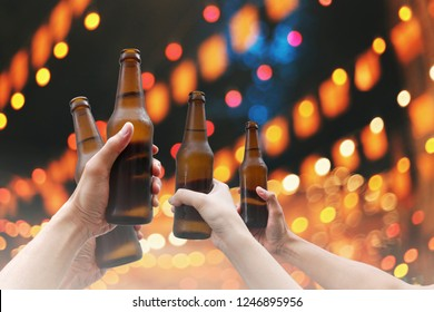 Hands holding beer bottles and happy enjoying harvest time together to clinking glasses at outdoor party on beautiful bokeh night light background.Celebration drinking beer in pub,bar.