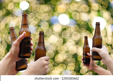 Hands holding beer bottles and happy enjoying harvest time together to clinking glasses at outdoor party on beautiful bokeh night light background.Celebration drinking beer in pub orbar.