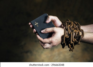 Hands holding a bible tied together with an old rusty chain.
