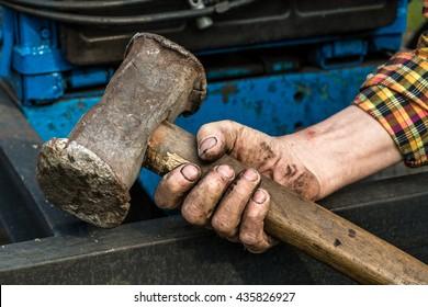 Hands holding a big hammer. Sledgehammer.