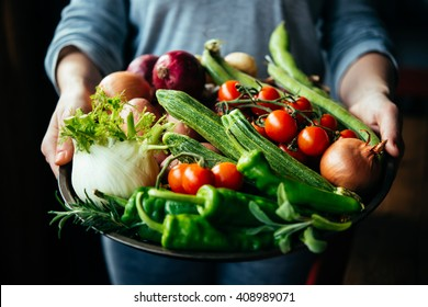 Hands holding big plate with different fresh farm vegetables. Autumn harvest and healthy organic food concept - Shutterstock ID 408989071