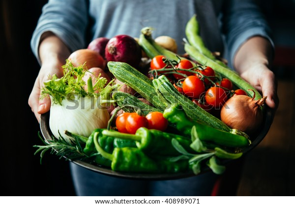 Hands holding big plate with different fresh farm vegetables. Autumn harvest and healthy organic food concept