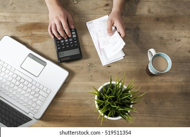 Hands holding bills and paying bills on computer