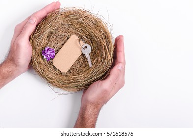 Hands holding a bird's nest or shelter with key inside, concept of a flat or apartment purchases