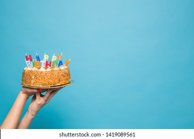 Hands holding a birthday cake with candles and the inscription birthday on a blue background. Copy Space