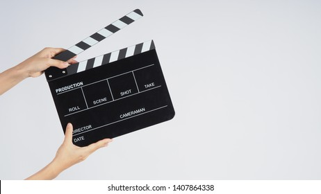 Hands is holding black Clapperboard or movie slate. it use in video production ,film, cinema industry on white background.