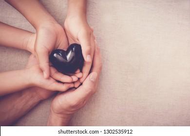 hands holding black heart, health insurance, mending broken family, mental health