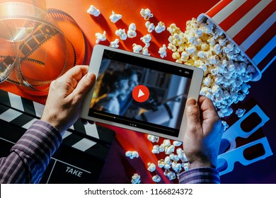 Hands holding a blank digital tablet, popcorn, 3D glasses and filmstrip, cinema and movie online streaming concept