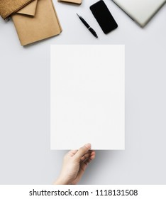 Hands holding blank paper sheet A4 size at table work space top view.
