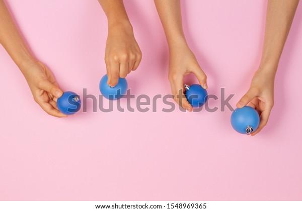 Hands holding blue Christmas bauble balls over light pink background