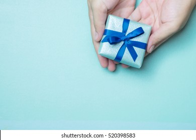 Hands holding blue wrapped gift box with blue ribbon as a present for Christmas, new year, mother day or anniversary on blue table background, top view