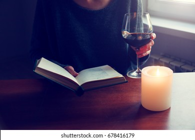 hands holding book and reading with glass of wine and cozy candle