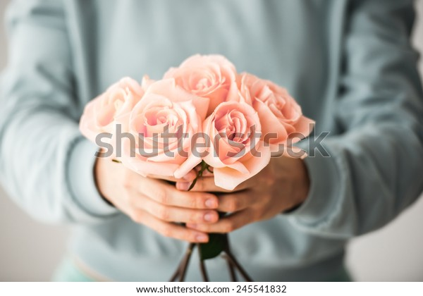 Hands holding bouquet of beautiful pink roses. Toned picture