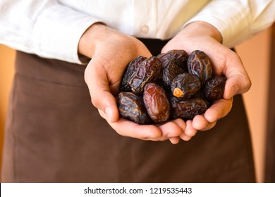 Hands holding a bowl of dates or Tamar copyspace. Holy month of Ramadan concept. Righteous Muslim Lifestyle. Fasting. Ramadan lantern, dates.Ramadan Kareem with dates. Ramadan Kareem cards.