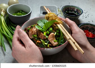 Hands holding bowl withc chinese udon noodles and beef, vegatables on the gray table.  Top view