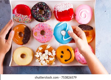 Hands holding box and choosing sweet doughnuts on gray stone background