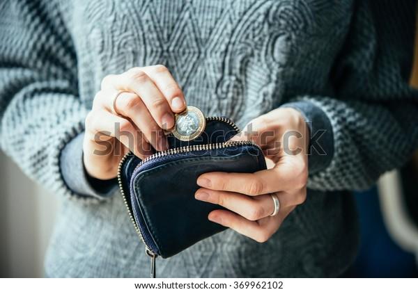 Hände, die Britische Pfund-Münze und kleine Geldbeutel halten
