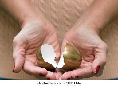 Hands holding Broken Golden Egg and Retirement Dreams