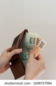 Hands holding a brown leather wallet and taking out a few hundred Czech crowns banknotes