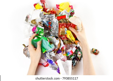 Hands holding a bunch of candy wrappers on a white background. Closeup.