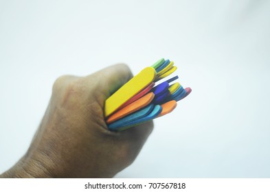 the hands are holding a bunch of colored wood stick on white backdrop