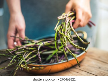 Hands holding a bunch of fresh asparagus. Selected focus and shallow DOF