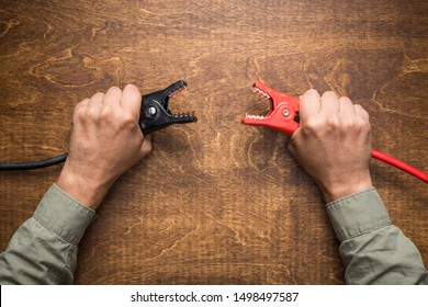 Hands holding car battery charging clamps. Concept of opposite polarity conflict or interaction.