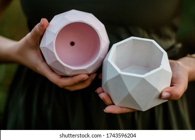 hands holding cement pot outdoors