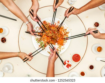 Hands holding chopsticks ready to toss into the air the mixture of shredded vegetables, ingredients and salmon. Yee Sang is often served during Chinese New Year.