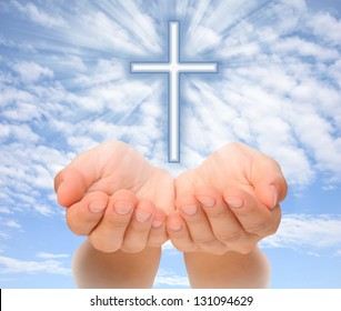 Hands holding Christian cross with light beams over sky