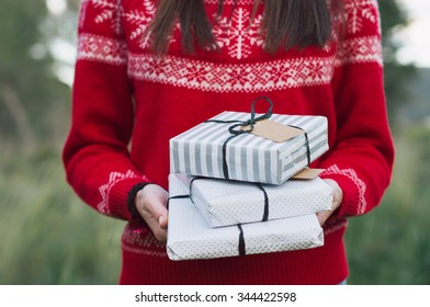 Hands holding Christmas gift. Background with christmas outfit