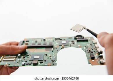 Hands holding cirquit board, laptop motherboard and tweezers with cpu microprocessor. Closeup view on white background isolated.