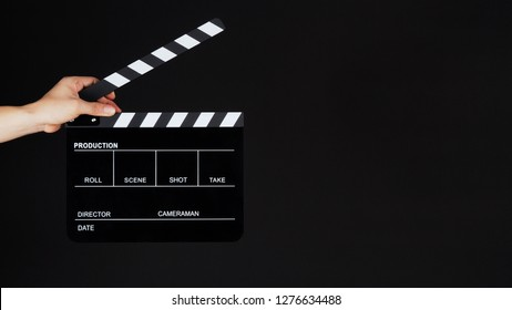 Hand's holding Clapperboard or movie slate use in video production ,film, cinema industry on black background.