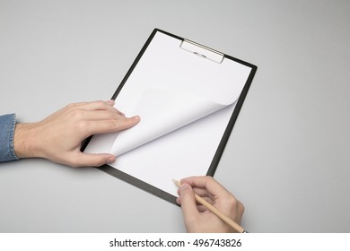 Hands holding clipboard and write/ Mock-up.