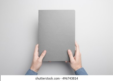 Hands holding closed Notebook. Blank cover Mock-up.